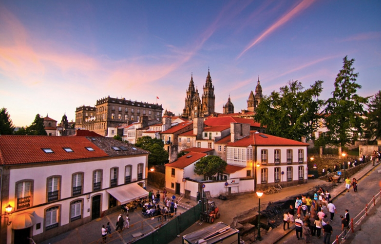 The Cathedral in the dusk over the red tiles roofs of Santiago de Compostela